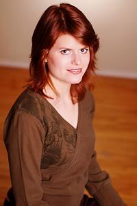 photograph of Megan Crewe, a redheaded woman looking up towards the camera